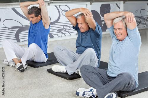 Männer dehnen sich im Fitnesscenter