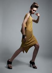 Stylish brunette female wearing yellow fashion dress