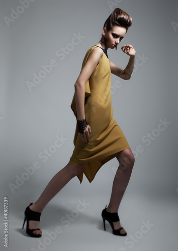 Stylish brunette female wearing yellow fashion dress