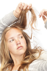 young blond girl looks at her hair