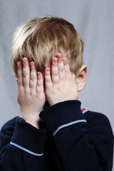 boy puts his hand over his eyes
