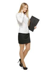 Full length of businesswoman walking talking on mobile phone