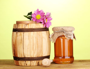 Sweet honey in jar and barrel with drizzler