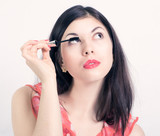 Portrait of pretty young woman applying mascara using lash brush poster