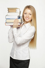 Young female holding heavy stack of books on shoulder