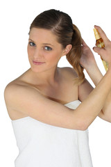 Blond woman using hair spray