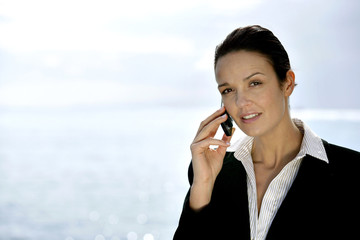 Businesswoman making phone call by the coast