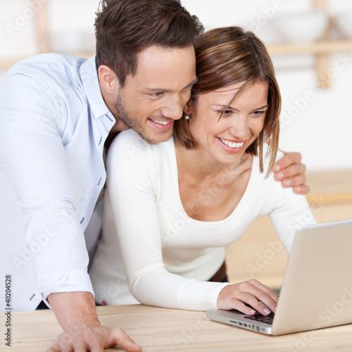 glückliches junges paar schaut auf dem laptop