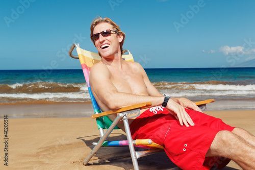 Portrait of happy young man relaxing on the beach