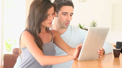 Couple at home websurfing on internet with tablet