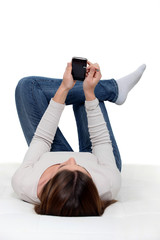 A woman lying and checking her phone.