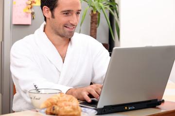 Breakfast in bathrobe with computer