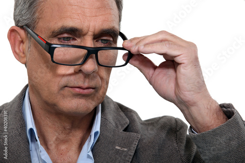 handsome mature man with lowered glasses