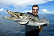 Постер, плакат: Happy fisherman holding a giant barracuda
