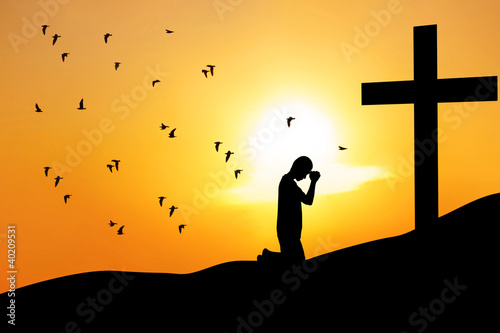 Christian background: man praying under the cross