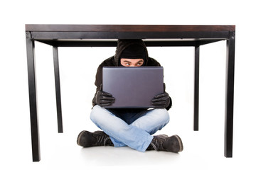 A hacker with laptop hidden under the office table, isolated on