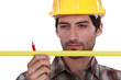 Man in a hardhat with a pencil and measure