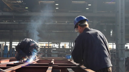 Workers grinding and welding in a factory