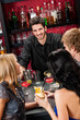 Barman chatting with friends drinking at bar