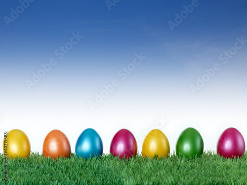 Happy Easter! Colourful eggs in the meadow with blue sky