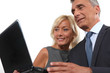 happy businessman and businesswoman looking at a laptop