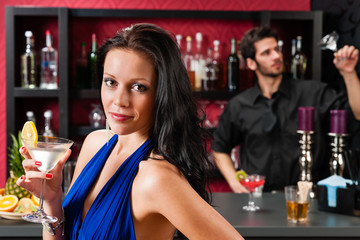 Glamour woman at bar holding cocktail