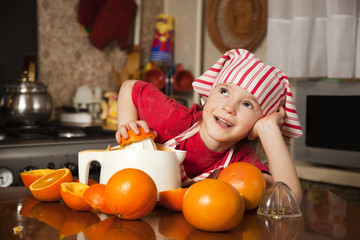 Little girl making fresh and healthy orange juice with kitchen a