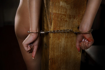 young naked girl hancuffed to a pole