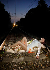 young beautiful girl lying on railway tracks