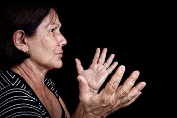 Woman talking and gesturing with her hands isolated on black