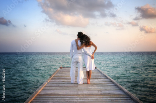 Sensual happy couple in white clothes on a pier (Maldives)