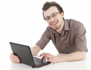 smiling young man in glasses using laptop