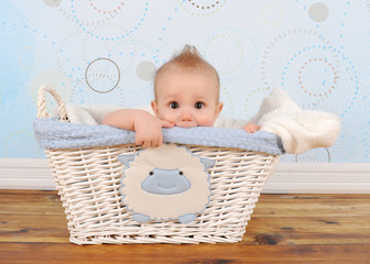 handsome baby boy peeking out of wicker basket