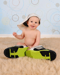 sweet baby boy wearing his Daddy's hat and sneakers