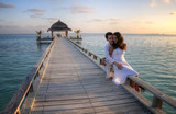 Sensual happy couple with white clothes on a pier (Maldives)