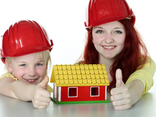Two girls with helmet show thumb up for building a house