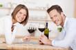 lachendes paar trinkt rotwein
