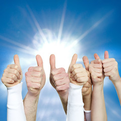 Close up of hands showing thumbs up in front of blue sky