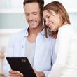 junges paar schaut auf tablet-computer