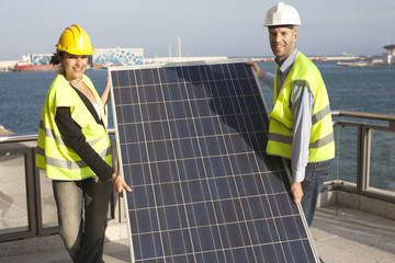 Engineers carry solar panel