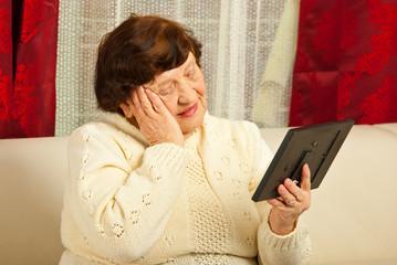 Sad elderly woman looking at photo frame