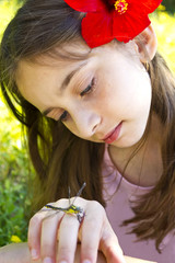Young girl perched on his hand looking dragonfly