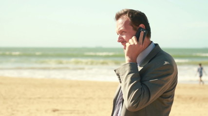 Businessman talking on cellphone by the sea