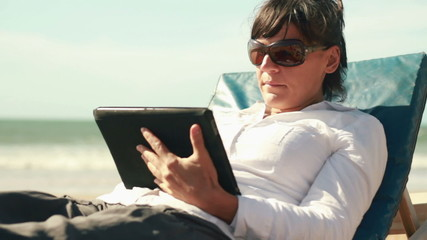 Businesswoman with tablet computer by the sea