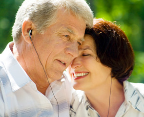 Senior couple in headset together, outdoors