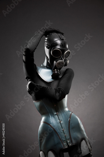 Woman in latex corset and gas mask