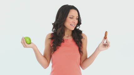 Young attractive woman choosing between an apple and a cookie