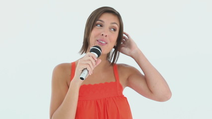 Girl singing into a microphone while smiling