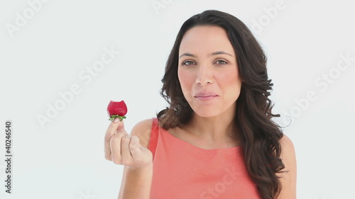 Girl sexily eats a part of a strawberry
