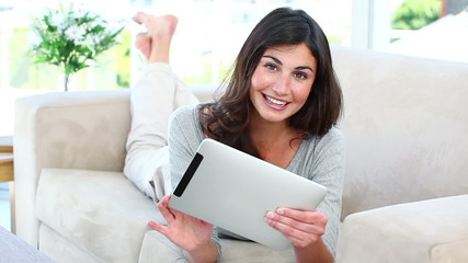 Woman using her tablet while smiling